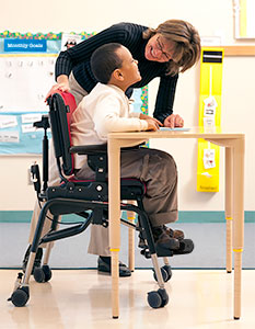Adaptive seating positions this young boy at a school desk and recieve help from the teacher who is bending over him