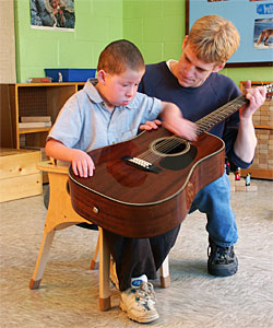 A young boy, in an autism classroom, focuses on strumming a guitar while his teacher patiently frets notes for him.