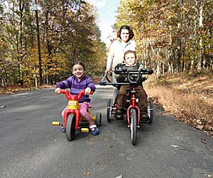 A cancer survival story continues with David riding his Rifton tricycle alongside his sister and Mom