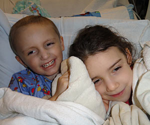 David Bryan, a cancer survivor, smiles as he snuggles in a comfy bed with his sister
