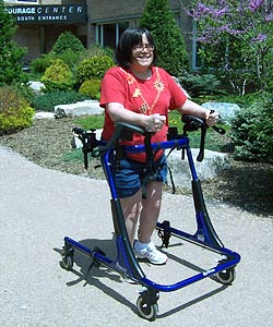 A smiling woman in a Rifton gait trainer (a device designed to offer more support than a typical quad walker) practices forward movement on four wheels.