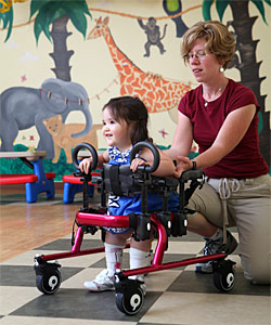 A therapist guides a special needs toddler in a red gait trainer in a playroom helping her perform early childhood intervention activities