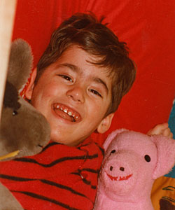 A young Duane lies on a red pillow cuddling with his pink pig and brown horse stuffed animals.