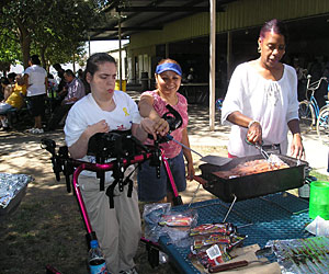 A disabled woman supported by a gait trainer, flips burgers on the bbq, helped by her Life Services personal advocate