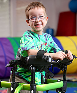 A young boy smiles in his green gait trainer