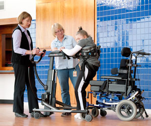 Two therapists assist a woman with disabilities to transfer from sitting to standing using the Rifton Transfer and Mobility Device