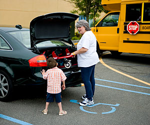 A mother places the folded Rifton Pacer gait trainer frame into the trunk of the car while her son looks on holding the side of the vehicle