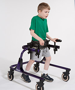 A young boy in a purple Rifton Pacer gait trainer practices walking in the posterior position on the equipment