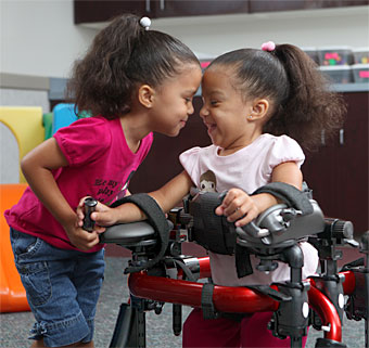 A little girl in an assistive technology device smiles at her sister who leans in close to her face.