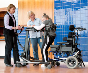 Two therapists help a young girl walk in the TRAM during a mobility product demo