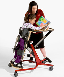A child with special needs properly positioned in a Prone Stander points to a picture in a book as her caregiver stands smiling over her