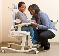A caregiver properly positions a young girl with special needs in a hygiene and toileting system from Rifton