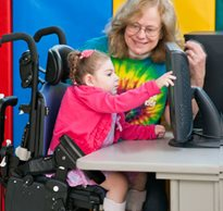 A teacher smiles at a child with cerebral palsy who is touching a computer screen from her adaptive chair