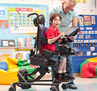 In a classroom setting, a young boy with cerebral palsy is seated in an adaptive chair while his teacher holds up a game for him to play with