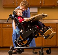 A practitioner adjusting the tilt-in-space feature on the Rifton Activity Chair to prepare a young boy for feeding.