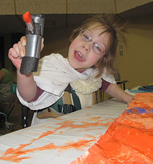 A child with disabilities in a Dynamic stander holds out her adaptive paint brush and smiles at the camera.