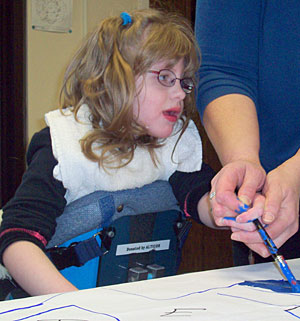A young child with disabilities in an adaptive stander gets assistance from her teacher to paint a figure in blue on the paper.