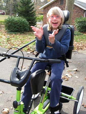 A girl smiles and claps her hands on a Rifton trike from Variety the Children's Charity