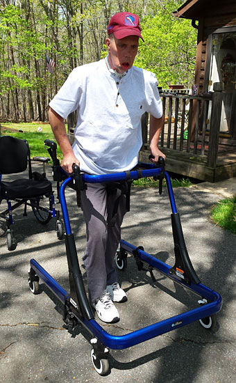 Jimmie Childress in a blue Rifton Pacer gait trainer walking at home.