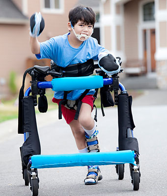 A young boy laughs as he walks down the driveway in a blue padded over-ground gait trainer