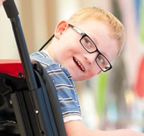 a boy with special needs in a Rifton Activity chair smiles at the camera.