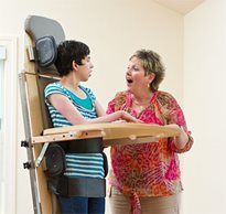 A therapist talks to an adult patient with a neurological condition during a therapeutic standing protocol
