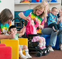 Educators and therapists sitting with children in a colorful special needs playroom, work as a team to help students practice their motor skills