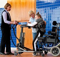 A special education teacher uses a Rifton TRAM to safely get a patient from sitting to standing