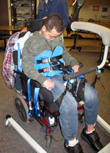 A therapist uses the SoloLift and then a TRAM to transfer a TBI patient.