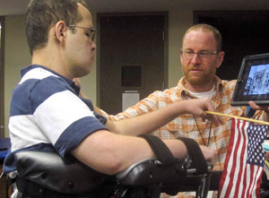 A TBI patient goes from sitting to raise his flag and pledge allegiance.