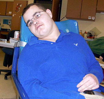 A TBI patient sits slumped down in a wheelchair with limited mobility and control.