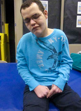 A TBI patient sits on a mat working on a variety of motor skills.