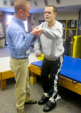 A TBI patient, with help from his therapist works on standing and stepping.