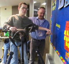 A TBI patient is successfully able to step consistently in a TRAM device with assistance from his therapist.