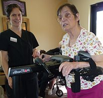 A stroke patient using a Rifton TRAM during a rehabilitation intervention session with her therapist