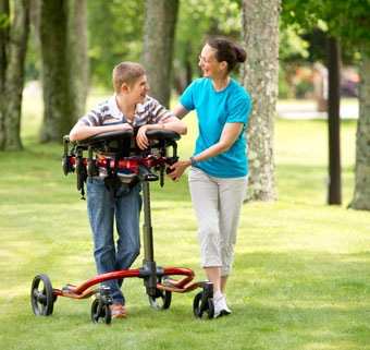 A young boy outside in a park using a dynamic gait trainer is safely guided by his therapist