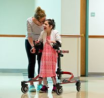 A young girl smiles as she uses a dynamic gait training walker with guidance from her therapist