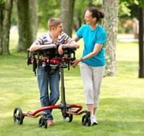 A therapist helps guide a young boy in a dynamic gait trainer as he walks on the grass in a park