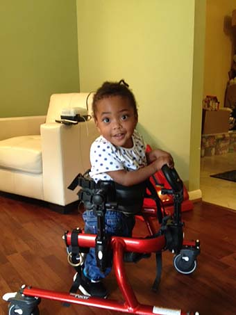 A young girl in a Rifton gait trainer smiles at the camera while practicing her motor skills to help with cognitive development