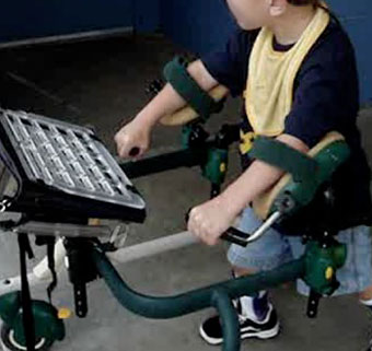 A young boy in a gait trainer using arm accessories to properly position the limbs downward in preparation for prompt reduction