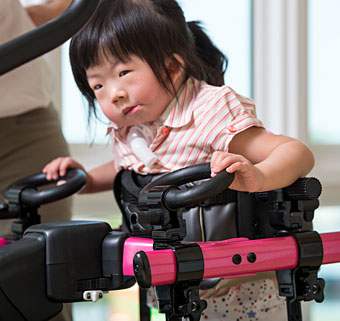 A young girl with a neurological condition uses a gait trainer to assist in walking