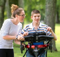 A therapist assisting a child with special needs in a dynamic gait trainer.