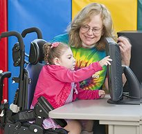 A teacher smiled at a special needs student seated in a adaptive chair practicing motor skills on a computer screen