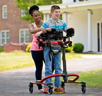 A caregiver assists a teenager using a medically necessary dynamic gait trainer outdoors