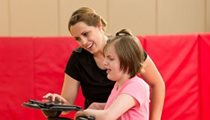A therapist helps properly position a child in a dynamic gait trainer using a checklist