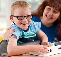 A school therapist helps a smiling young boy with special needs engage in classroom activities