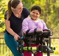 A therapist with her arms around a child with disabilities smiles as she practices dynamic movement in her gait trainer