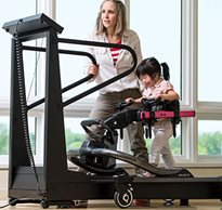 A young girl with special needs uses the treadmill to practice gait training helped by her therapist
