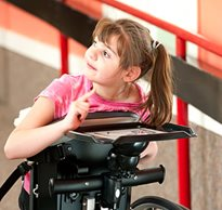 A young girl positioned in a standing mobility device points to her communication tray.