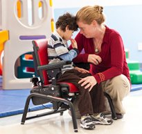 A therapist places her head on the head of a boy with disabilities who is sitting with support in an Activity chair helping him use problem solving skills for cognitive development